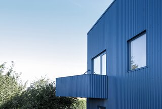 A Blue House Clad With Corrugated Steel Blends Into the Scandinavian Sky